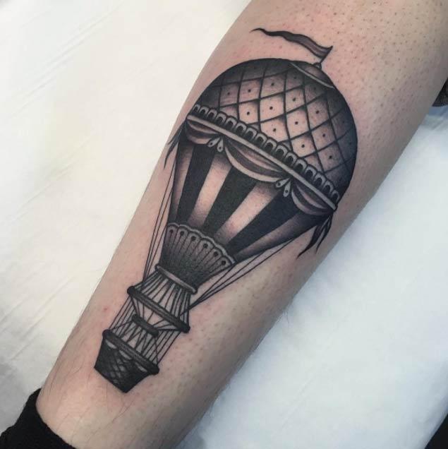 Brazo con un tatuaje de globo aerostático en tonos grises estilo antiguo