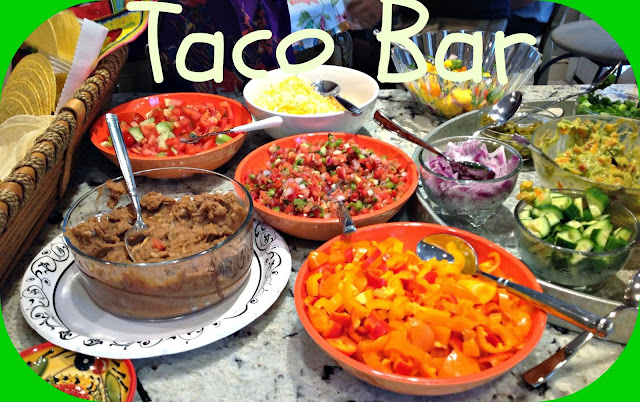 taco bar with bowls of vegetables, refried beans, bean, and salsa