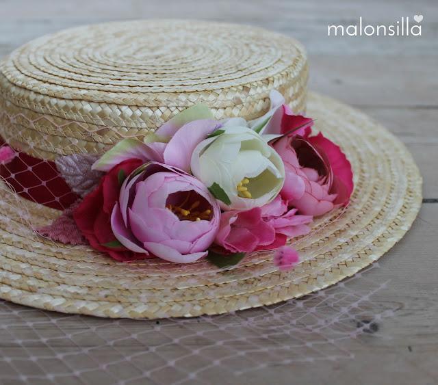 Primer plano de canotier con flores rosas sobre suelo de madera antguo