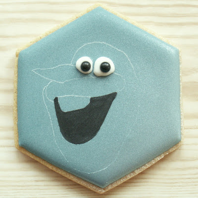 Blue cookie with Olaf's mouth painted black and eyes piped in royal icing, photo by Honeycat Cookies