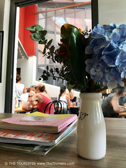 Magazines and a bunch of flowers in a white vase on a wooden table. People in the background eating in the outdoor space of the cafe.