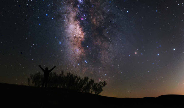A man looking at the starry night sky of Varzaneh desert.