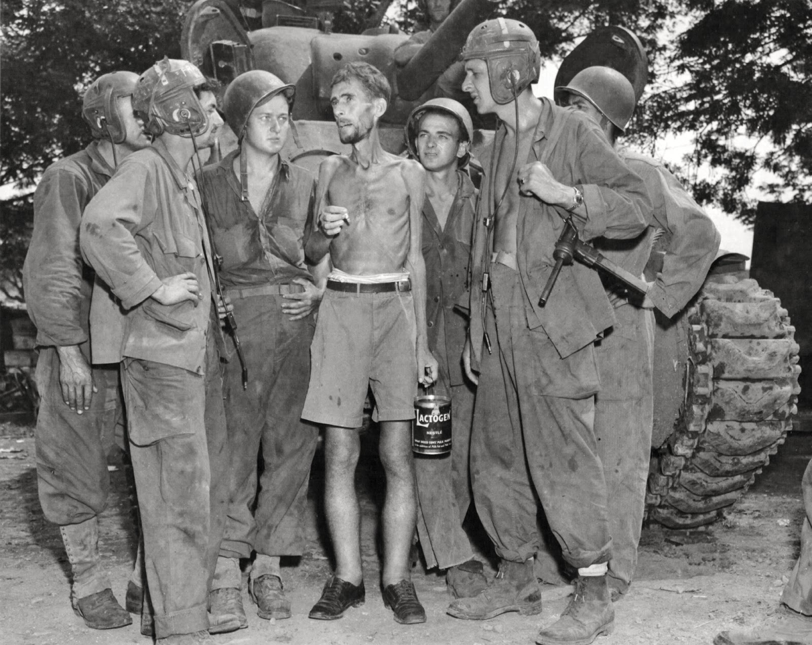 American tank crews listen as Bernard Herzog (US citizen) who was liberated from the camp of Santo Tomas, Manila, Philippines