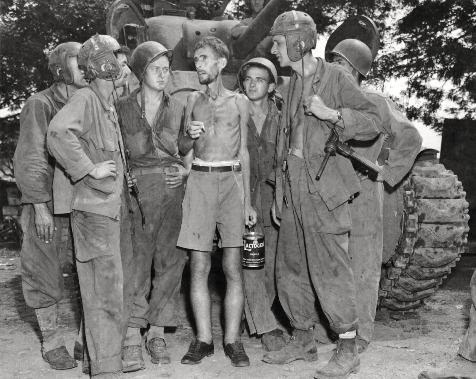 Tripulaciones de tanques estadounidenses escuchan a Bernard Herzog (ciudadano estadounidense) que fue liberado del campamento de Santo Tomás, Manila, Filipinas.