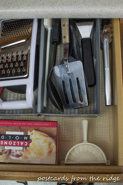 Cooking utensils stored in a drawer next to the stove plus lots of other great ideas for kitchen organization.