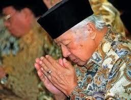 Soeharto sedang berdoa dan batu cincin miliknya terlihat di jemarinya