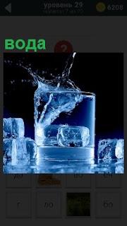 Стакан воды с кубиками льда, которые так же лежат рядом на поверхности стола