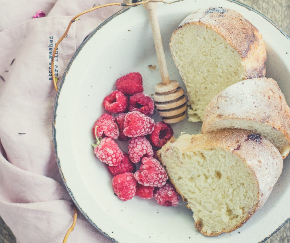 A bowl filled with slices of thick bread and frozen raspberries