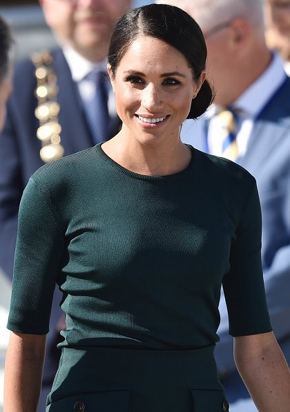 Meghan Markle wore Givenchy patch pocket pencil skirt, and Vanessa Tugendhaft Charm earrings, carried Strathberry handbag