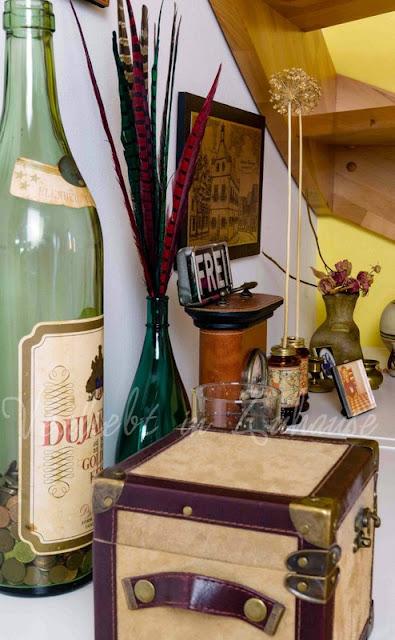 Flohmarkt-Flair mit umfunktionierten Flaschen als Spardose, alten Schildern, Kerzen und Boxen