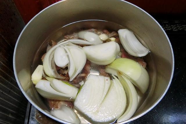 丸鶏の骨と野菜類を鍋に入れて鶏ガラスープを作ります。