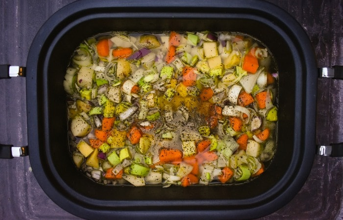 Vegetable Soup ingredients in a slow cooker with stock