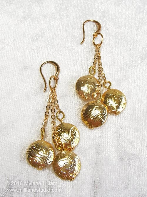 Golden vermeil lentil earrings dangling from fine chain
