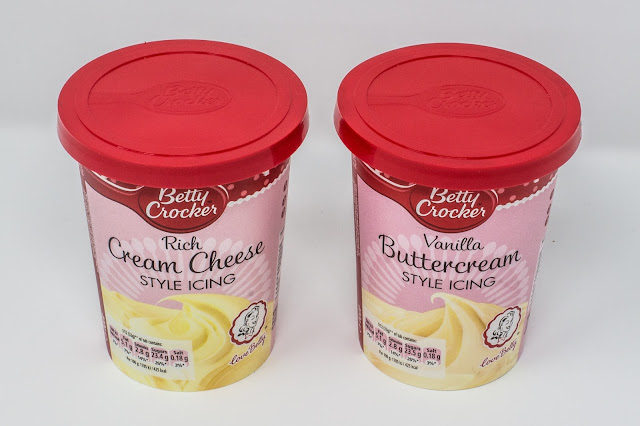 A tub of Betty Crocker's Rich Cream Cheese Style Icing and a tub of Vanilla Buttercream style icing