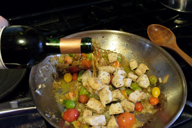 White wine and chicken being added to the tomatoed, onion, and garlic that is in the skillet on the stove.
