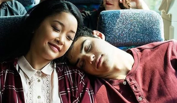 screen shot of a scene from the movie in which Peter is leaning his head on Lara Jean's shoulder