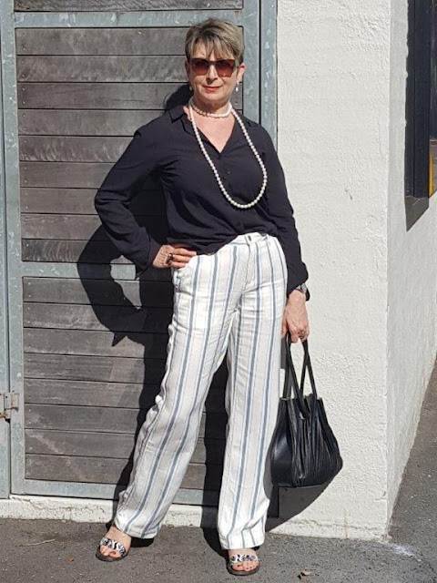 White striped pants/black blouse and pearls