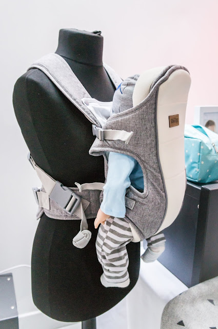 mannequin wearing baby carrier on display against white background at nuby big reveal event
