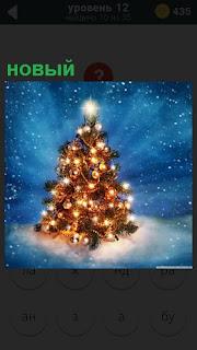 На снегу стоит наряженная елка в новый год с огнями и гирляндами