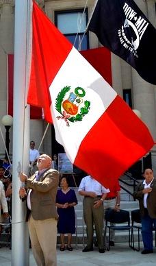 Foto de peruano izando la bandera del Perú