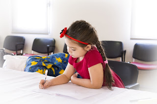 Young girl writing at a table.