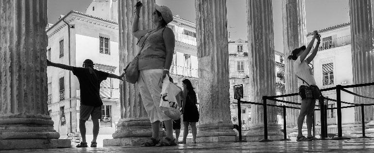 Photo panoramique de touristes autour des colonnes de la Maison carrée de Nîmes.