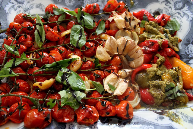Grilled strings of tomatoes on the vine, whole garlic, pepper slices and seasoned with pesto and balsamic