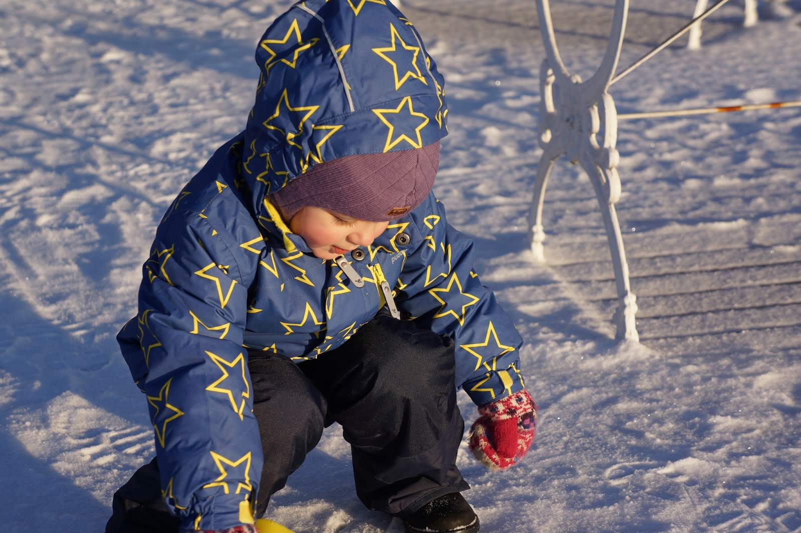 a child playing in snow wearing ski clothing