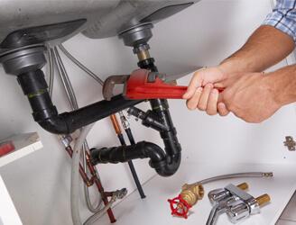 Plombier en train de réparer des sanitaires.