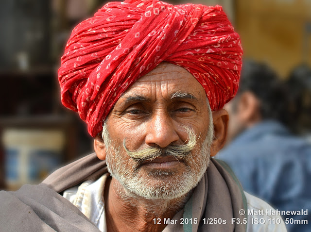 Rajasthani turban; pagari; moustache; red turban; Matt Hahnewald Photography; Facing the World; photography; photo; image; outstanding; fantastic; favourite; superior; excellent; inspirational; vibrant; breathtaking; Nikon D3100; Nikkor AF-S 50mm f/1.8G; prime lens; 50mm; 4 : 3 aspect ratio; horizontal format; closeup; colour red; portrait; portraiture; headshot; en face; front view; outdoor; colour; colourful; world cultures; cultural; character; personality; real people; human; human head; human face; human eyes; facial expression; eye contact; Rajasthani pagari; turban; consent; empathy; rapport; encounter; relationship; emotion; mood; environmental portrait; ethnic portrait; travel; travel portrait; travel destination; tradition; Jaisalmer; Rajasthan; India; one person; male; adult; Indian man; posing; authentic; incredible; awesome; Rajasthani man; street portrait