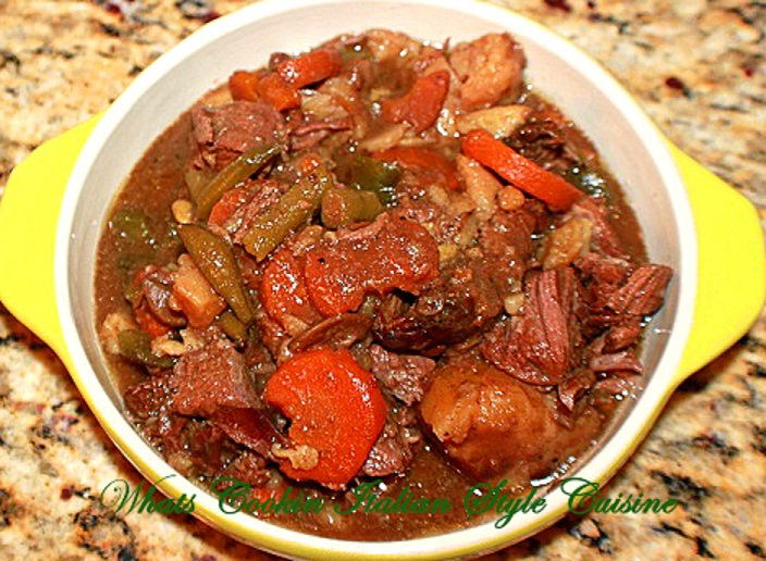 This is a yellow ceramic dish filled with beer stew that has been slow cooked in a slow cooker all day in a sauce with peas, carrots, potatoes, pot roast that is juicy and fork tender beef roast