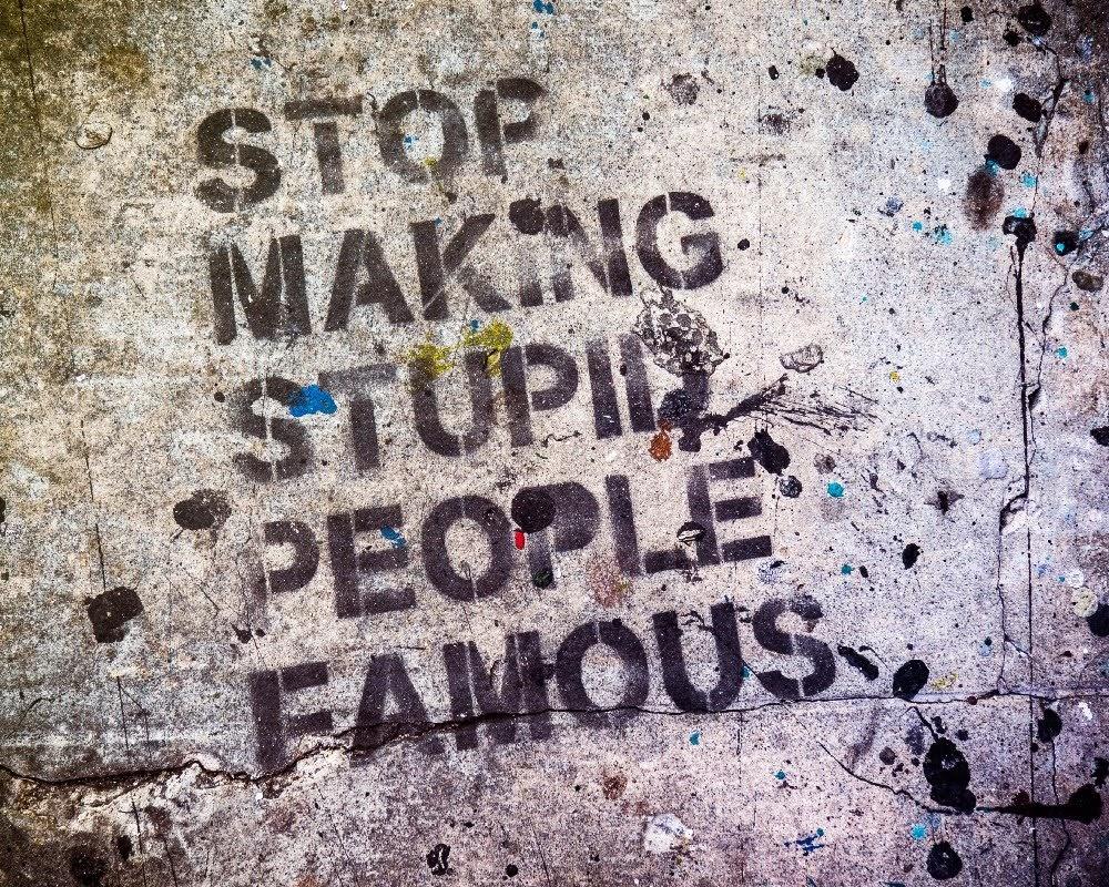 """""""Pareu de fer famosa a gent estúpida"""" pintat a una paret."""