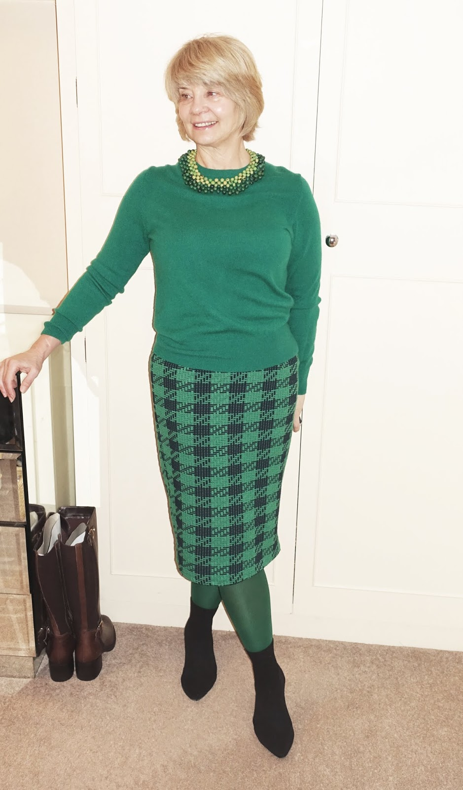 Over-50s blogger Is This Mutton? in an all-green outfit of jumper, necklace, skirt and tights.