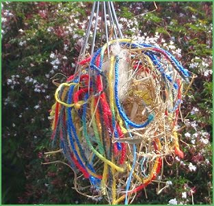 Bird nesting materials: yarn, pet hair & more in a wire whisk