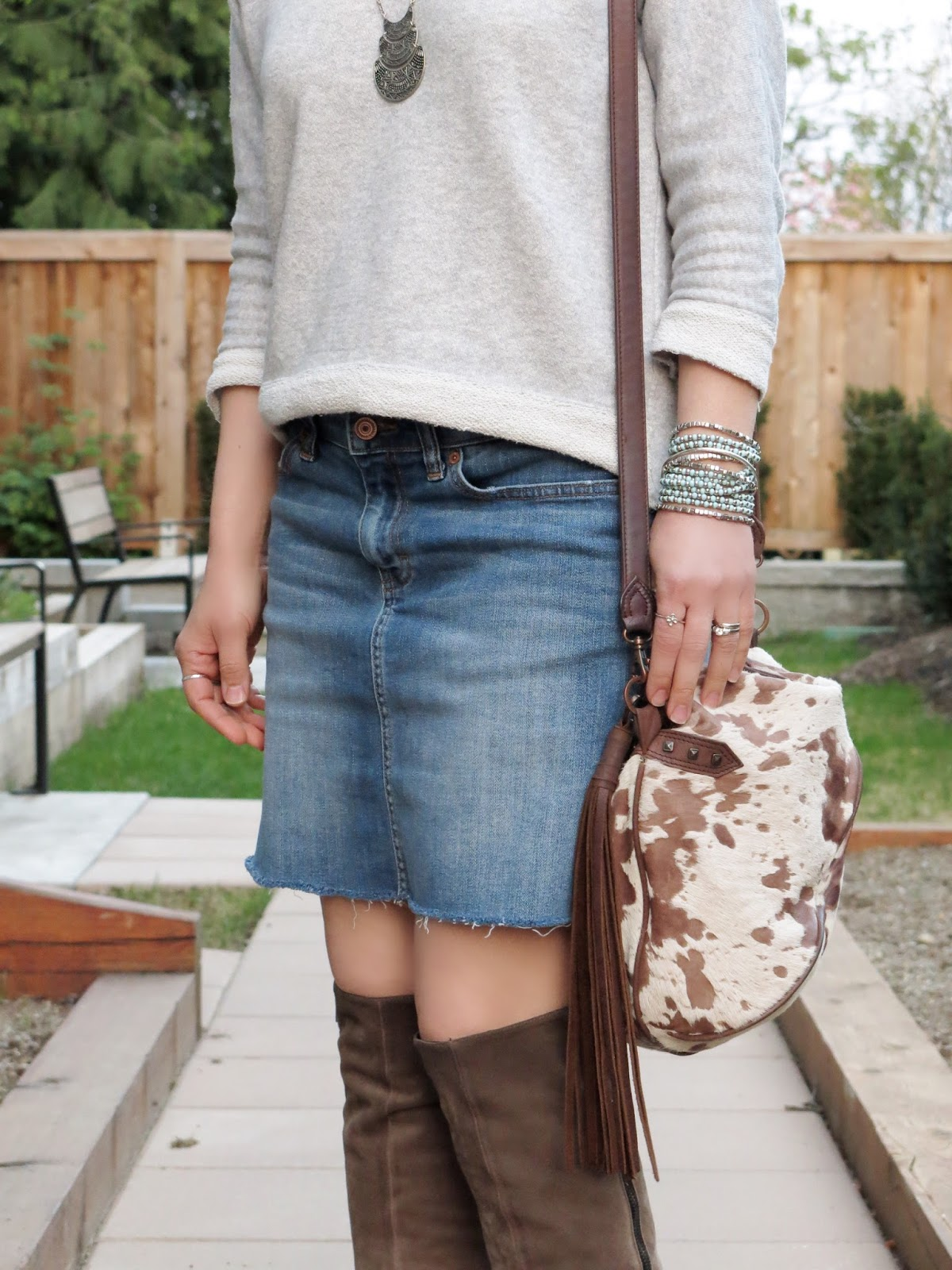 raw-hemmed denim skirt, sweatshirt, suede knee boots, and pony-hair bag