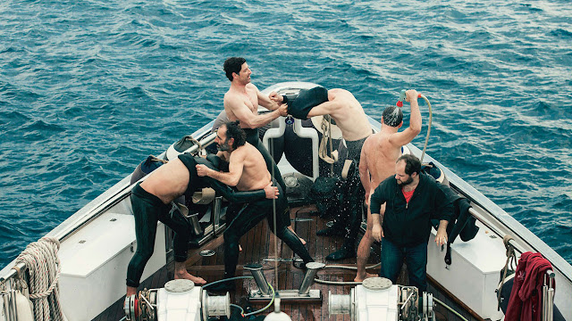 Men helping each other to get out of wet, rubber suit. The one who stands apart in the group is fully-clothed, socially awkward Dimitris
