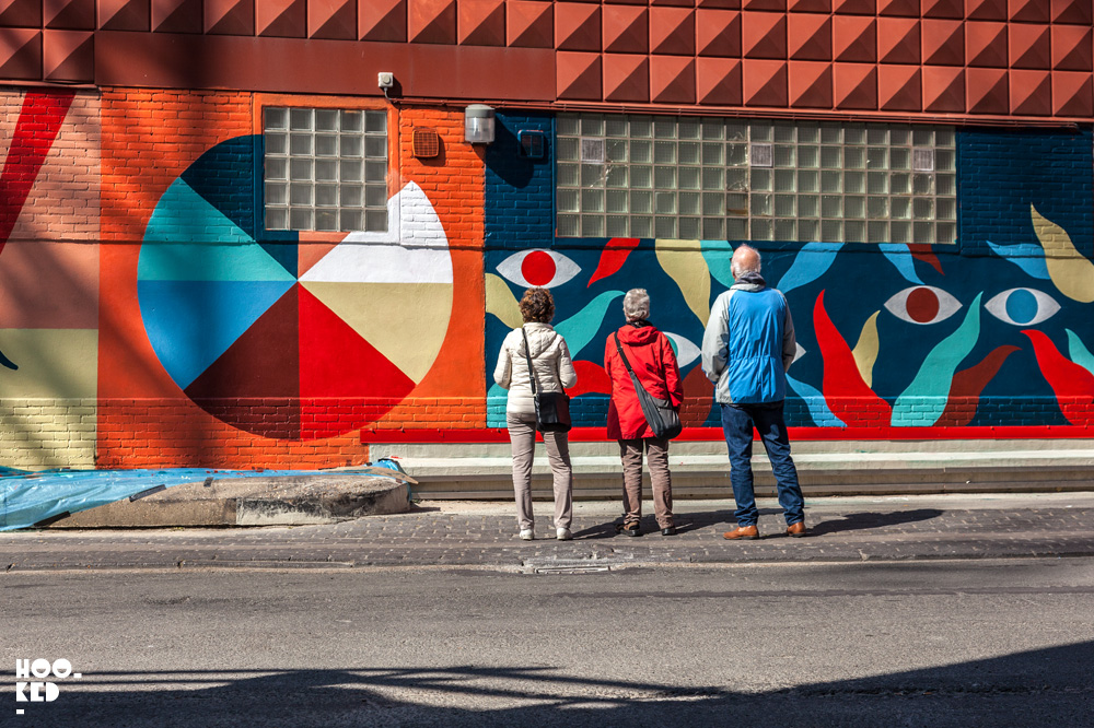 Tourists stood in front of artist Hell'O Collective Mural in Ostend, Belgium.