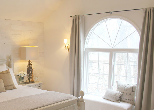 bench at window and modern farmhouse style and neutrals in master bedroom of Hello Lovely Studio's fixer upper