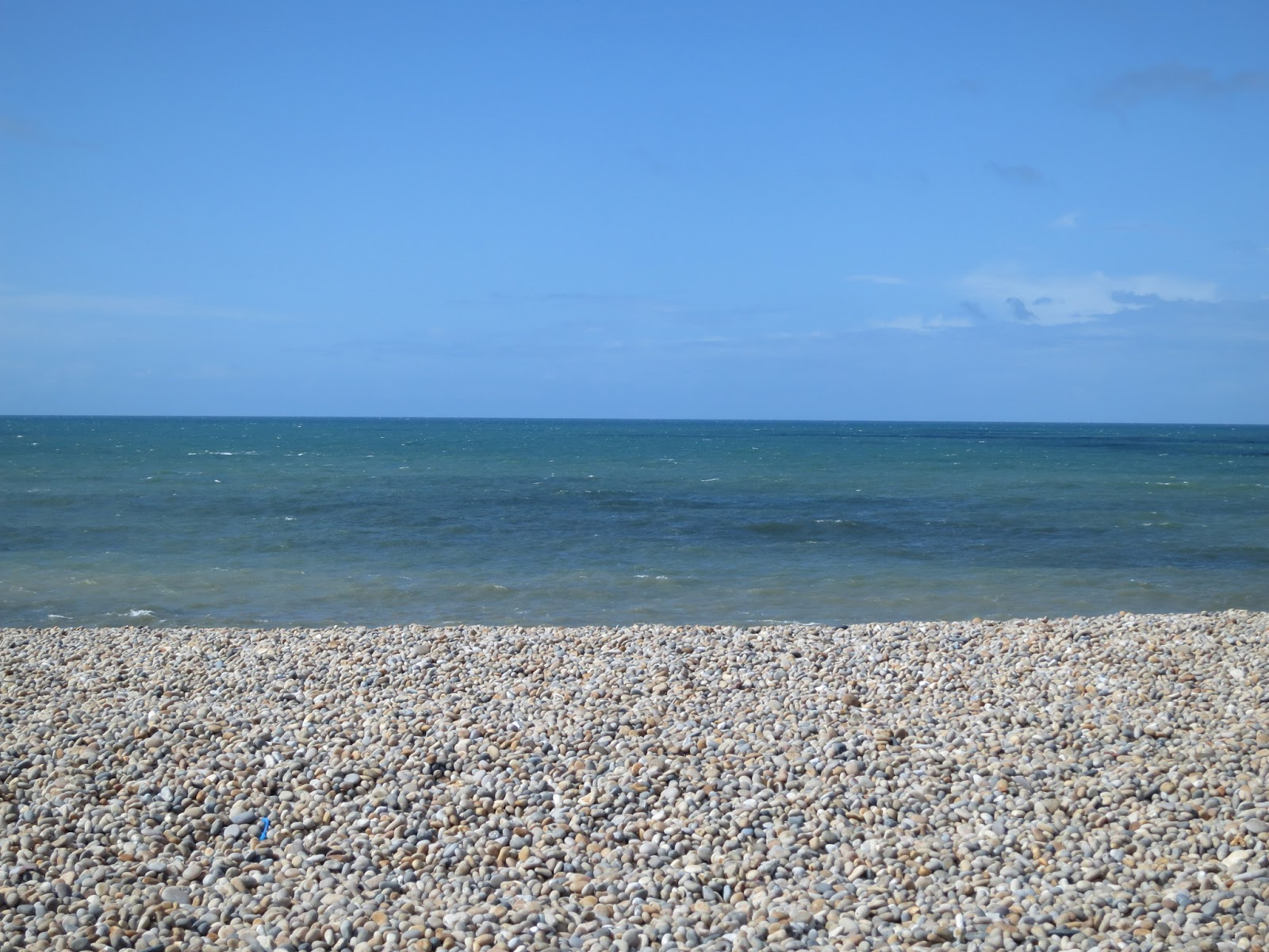 Three bands of colour - grey pebbles, dark blue sea, bright blue sky.