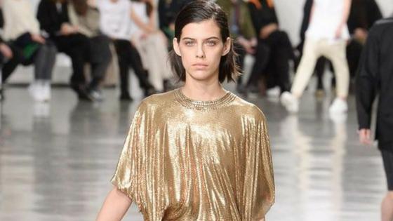 Imagem ilustrativa. Modelo em desfile de moda a usar um look dourado