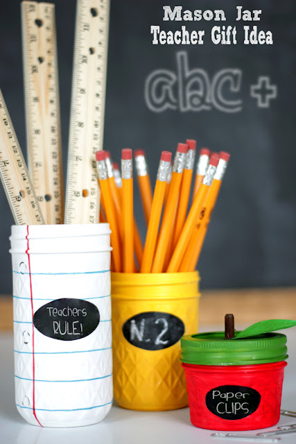 Note pad jar holding rulers, yellow jar holding pencils and little red apple jar holding paper clips.