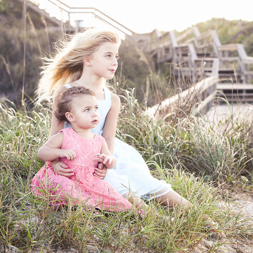 Sisters pose for family photos on the beach