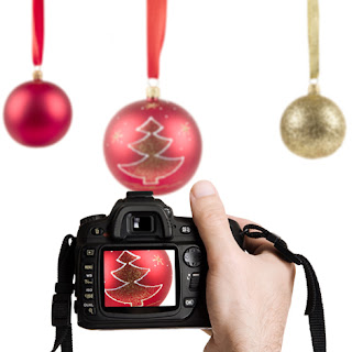 Photo of a Hand Holding a Camera and Three Hanging Christmas Balls