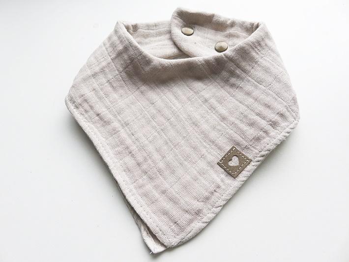 Beigefarbenes Baby-Sabbertuch aus Musselin mit Snappap Etikett und Druckknopfverschluss