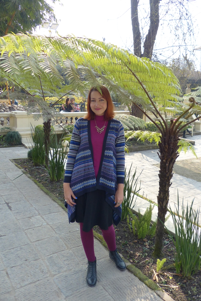 Blue patterned cardigan over fuchsia top with black skirt and fuchsia tights