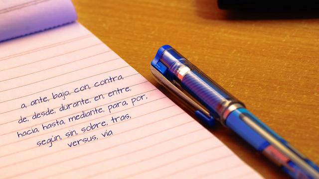 Cuaderno con la lista de preposiciones y bolígrafo.