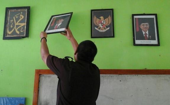 anggota Pemuda Panca Marga Kota Padang menurunkan foto Presiden Joko Widodo dan Wakil Presiden Jusuf Kalla di SDN 38 Lubuk Buaya, Padang, Rabu (3/1). PPM PADANG