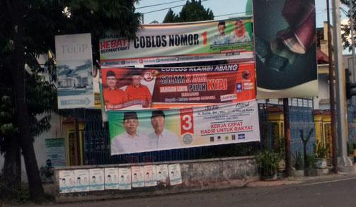 Alat peraga kampanye dari tiga paslon yang terpasang di sudut jalan