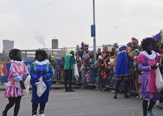 Costumed Piets distributing cookies to the children, Zaandam, The Netherlands