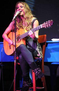 Foto de Debi Nova cantando con su guitarra